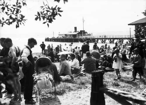 People on the beach at Days Bay, Lower Hutt, in 1930. Includes a man in a bathing costume, women with parasols and sun hats and a baby in a pram in the foreground. The ferry 'Muritai' is docked at the Days Bay Wharf in the background. Photographer: Sydney Charles Smith S C Smith Collection Reference number: 1/2-048206-G Permission of the Alexander Turnbull Library, Wellington, New Zealand, must be obtained before any re-use of this image.