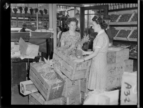 Selling pineapples at Franklins fruit shop, corner of Queen Street, Auckland. Whites Aviation Ltd :Photographs. Ref: WA-11653-G. Alexander Turnbull Library, Wellington, New Zealand. http://natlib.govt.nz/records/23072683